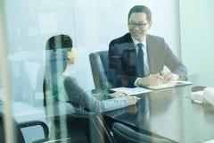 Kollegor som möter i konferensrum, skott till och med exponeringsglas arkivfoton