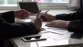 Kollegor som planerar samman med graf i kontoret arkivfilmer