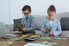 Kollegor som räknar valuta, medan sitta på soffan royaltyfri bild