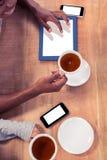 Kollegor som rymmer kaffekoppar, medan genom att använda teknologier Arkivbilder