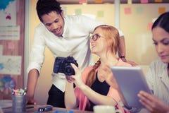 Kollegor som rymmer kameran med affärskvinnan som använder den digitala minnestavlan i förgrund Arkivfoton