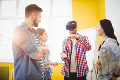 Kollegor som ser den bärande virtuell verklighethörlurar med mikrofon för affärsman royaltyfria bilder