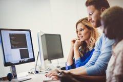 Kollegor som tillsammans arbetar i företagskontor arkivbild
