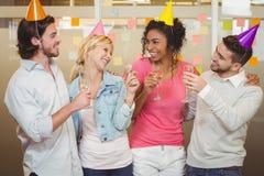 Kollegor som tycker om födelsedagpartiet med champagne Arkivbilder
