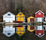 Kolnes in Norwegen - januray 10, 2018: Vier alte hölzerne Bootshäuser reflektierten sich im ruhigen Ozean Norwegerwestküste Stockfoto