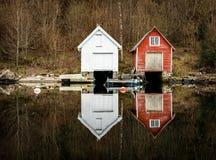 Kolnes in Norwegen - januray 10, 2018: Zwei alte hölzerne Bootshäuser reflektierten sich im ruhigen Ozean Norwegerwestküste, Norw Lizenzfreies Stockbild