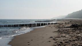 Kolobrzeg Polen 28 Juli 2018 Dimmig morgon på det synliga folket för polsk strand, havet, skärmarna och trävågbrytarna royaltyfri foto