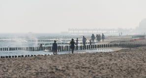 Kolobrzeg, Polen 28 Juli 2018 Nevelige ochtend op Poolse strand zichtbaar vaag twee vrouwen die het noordse lopen en hout uitoefe stock foto's