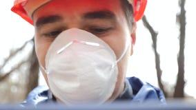 ?kologisches Krisenfoto Ein Mann in einem Sturzhelm und Respirator mit Maßen einer Tablette der Verschmutzungsgrad des Abwassers stock video footage