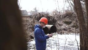 ?kologisches Krisenfoto Ein Mann in einem Sturzhelm und Respirator mit Maßen einer Tablette der Verschmutzungsgrad des Abwassers stock footage