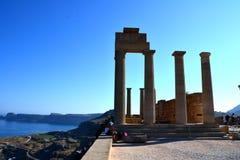 Kolommen op hellenistic stoa van de Akropolis van Lindos, Rhodos, Griekenland, Blauwe hemel, olijfboom en mooie overzeese mening  Stock Fotografie