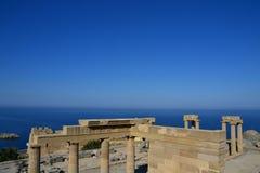Kolommen op hellenistic stoa van de Akropolis van Lindos, Rhodos, Griekenland, Blauwe hemel, olijfboom en mooie overzeese mening  Royalty-vrije Stock Afbeelding