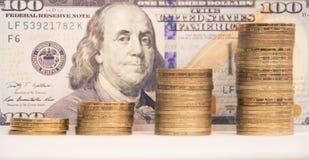 Kolommen van gouden muntstukken van verschillende hoogten tegen de achtergrond van honderd dollarsbenaming stock fotografie