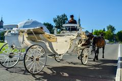 Kolomna, Russia - August 11, 2018. Elegant white carriage with coachmen in black hat and brown horses carrying tourists stock images