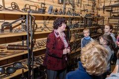 Kolomna, Russia - January 03, 2017: Female-guide Blacksmith Settlement museum visitors among Royalty Free Stock Photo