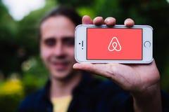 KOLONIA NIEMCY, Maj, - 06, 2018: Zbliżenie trzyma białego iPhone z AIRBNB logem na ekranie młody człowiek Zdjęcia Stock