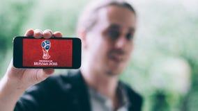 KOLONIA NIEMCY, Maj, - 06, 2018: Zbliżenie trzyma białego iPhone z FIFA WORLDCUP 2018 logem na ekranie młody człowiek Zdjęcia Stock