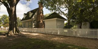 Koloniaal huis achter witte piketomheining stock fotografie