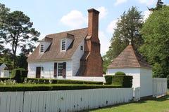 Koloniaal stijlhuis met tuin tegen blauwe hemel royalty-vrije stock afbeelding