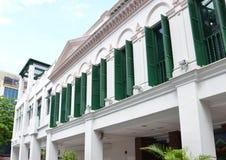 Kolonial byggnad med färgade träfönster för gräsplan Arkivfoto