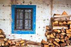 Kolonialt fönster och vedträ Arkivbild