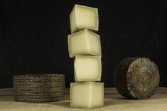 Kolonn av stycken av halvhård ost och två Manchego ostar i bakgrund Royaltyfria Foton