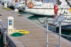Kolonn som levererar elektricitet och sötvatten av hamnbryggan arkivfoton