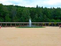 Kolonnade von Badekurort, von Brunnen, von Leuten, von Bäumen und von Wald Luhacovice im Hintergrund lizenzfreies stockbild