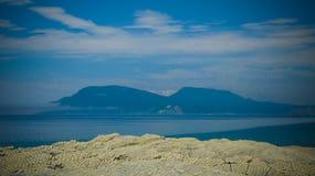 Kolonnbasaltbildande av Stolbchaty udde på Kunashir, kuril öar, den Ryssland och Hokkaido ön på bakgrund, Japan royaltyfria foton