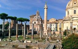 Kolonnen för Trajan ` s i Rome, Italien omgav vid historiska byggnader och fördärvar Royaltyfri Foto