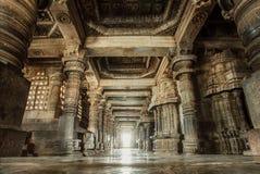 Kolonner och tom korridor inom den 12th århundradestentemplet Hoysaleswara, nu Karnataka stat av Indien Arkivfoton