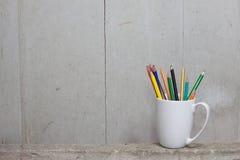 Kolorów ołówki łamający na Białym kubku kłaść na cemencie Obraz Stock