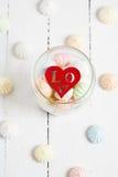 Kolorów zephyrs i drewniana postać na białym drewnianym stole serce w szklanym słoju Pojęcie St walentynki ` s dzień Fotografia Stock
