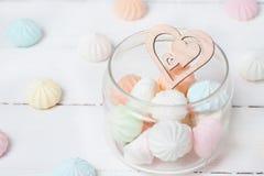 Kolorów zephyrs i drewniana postać na białym drewnianym stole serce w szklanym słoju Pojęcie St walentynki ` s dzień Zdjęcie Stock