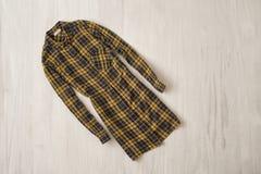 Kolor żółty chekcered koszula na drewnianym tle modny pojęcie zdjęcie royalty free