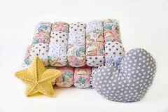 Kolor żółty dział pięcioramienna gwiazda kształtującą poduszkę, patchworku comforter i serce kształtującą poduszkę na białym tle, zdjęcie royalty free