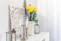 Kolor żółty kwitnie w ceramicznej wazie z drewnianymi candlesticks i lant zdjęcie royalty free