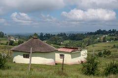 Kolor żółty malował borowinową budę, rondavel z pokrywającym strzechą dachem w Transkei terenie/, Dziki wybrzeże, Południowa Afry zdjęcie stock