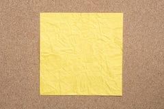 Kolor żółty marszcząca papier notatka na korkowym tle Fotografia Stock
