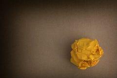 Kolor żółty miął papierową piłkę na brown tle Zdjęcia Stock