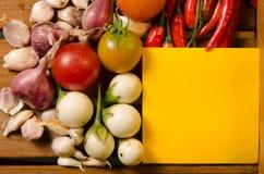 Kolor żółty notatka z chili, pomidor, szalotka i czosnek na drewnie, deseniujemy tło Fotografia Stock