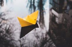 Kolor żółty papierowa łódź w miasto ulicy kałuży Jesień optymizm fotografia stock
