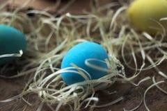 Kolor żółty, zieleń i błękitni Wielkanocni jajka na drewnianym stole obok, Zdjęcie Stock