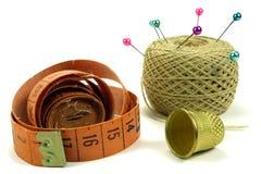 Kolor szpilki dla szyć z zwitką nici, naparstek i pomiarowa taśma na białym tle, Obraz Stock