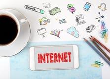 kolor tła pojęcia, niebieski internetu Telefon komórkowy i filiżanka na białym biurowym biurku Zdjęcie Royalty Free