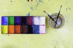 Kolor taca zawiera różnorodnego kolor z paintbrush w wodnej filiżance Obraz Stock