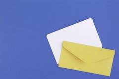 Kolorowa żółta koperta i biała pusta karta na błękitnym tle Obrazy Royalty Free