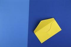Kolorowa żółta koperta na błękitnym tle Obraz Royalty Free
