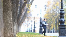 Kolorowa aleja w jesień parku z latarniami ulicznymi, liście jest fallng Nastoletnia sylwetka w starego stylu kurtki bombowiec zbiory wideo