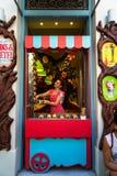 Kolorowa bajka tematu shopfront dekoracja cukierki sklep z pięknym młoda dama sprzedawcą ono uśmiecha się w menchiach ubiera zdjęcia stock